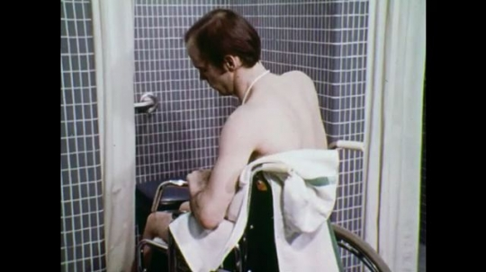 UNITED STATES: 1970s: man removes side from wheelchair. Man slides onto shower seat. Man pulls shower curtain across