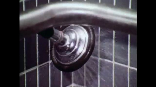 UNITED STATES: 1970s: man turns on shower. Man tests water temperature