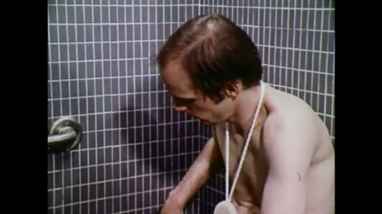 UNITED STATES: 1970s: man sits in shower cubicle. Man undoes tube with teeth. Man puts gel on arm. Man turns on shower