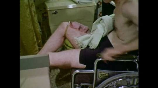 UNITED STATES: 1970s: man lifts leg onto wheelchair. Man dries legs with towel.