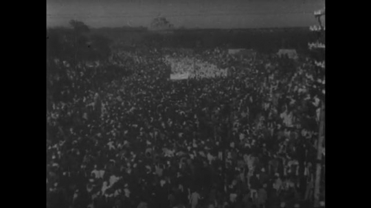 INDIA: 1940s: Gandhi carried to river in India through crowds