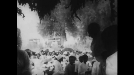 INDIA: 1940s:  Gandhi sits on ground in front of crowd.