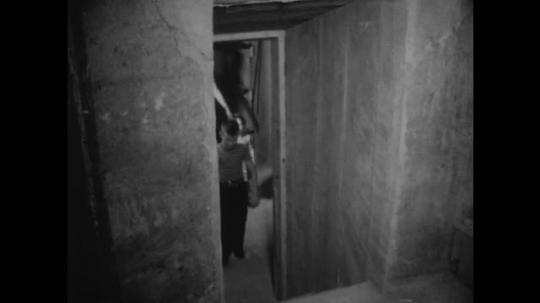 UNITED STATES: 1910s: man and children walk through bunker.
