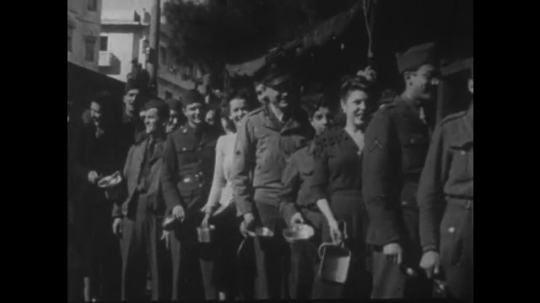 UNITED STATES: 1940s: actors visit soldiers on frontline to entertain. People in queue.