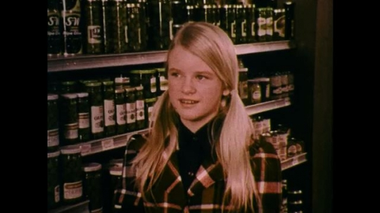 UNITED STATES: 1970s: girl stands by shelf in supermarket