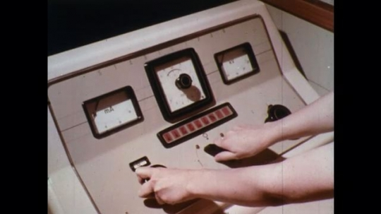UNITED STATES: 1960s: nurse turns buttons on medical machine. Nurse looks at patient through glass.