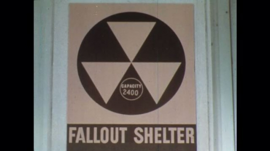 UNITED STATES: 1960s: fallout shelter for 2400 people. Sign for shelter. View of building.