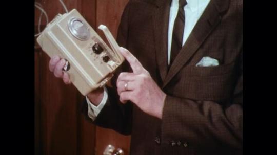 UNITED STATES: 1960s: man holds Geiger counter. Man puts machine on shelf. Man talks to camera. Man walks to desk.