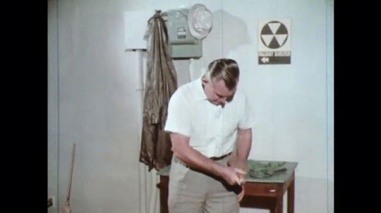 UNITED STATES: 1960s: man brushes down clothes. Man washes hands and wash with soap in bowl.