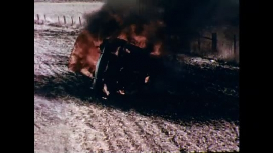 UNITED STATES: 1970s: car in flames on road. Picture of car hit by train. People in street. Traffic on road.