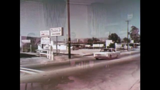 UNITED STATES: 1970s: car stops at railway junction. Learner driver stops at railway crossing. Policeman talks to drivers.