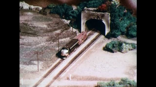 UNITED STATES: 1970s: model train appears from tunnel. Cars cross in front of train.