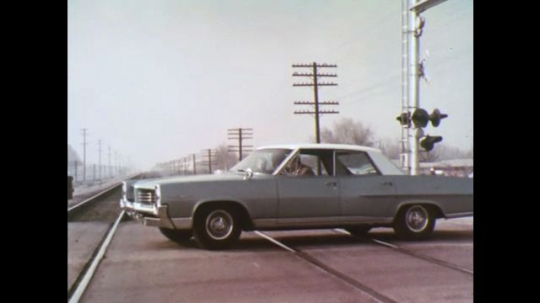 UNITED STATES: 1970s: car stuck on tracks. Men run from car on crossing. Men wave at train.