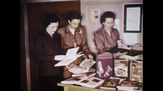 UNITED STATES: 1960s: ladies flick through books in library. Ladies meet in library.