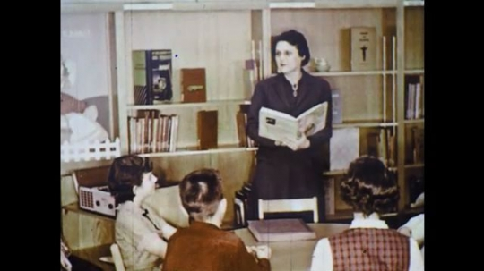 UNITED STATES: 1960s: lady reads to pupils in library.