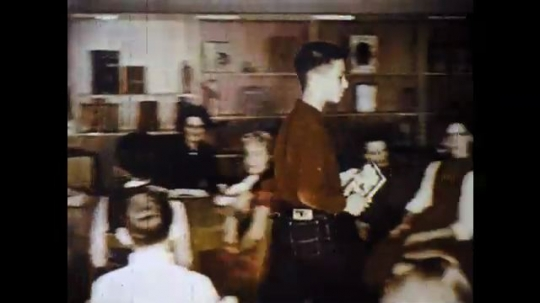 UNITED STATES: 1960s: boy walks to teacher. Lady takes book. Students point to desk.