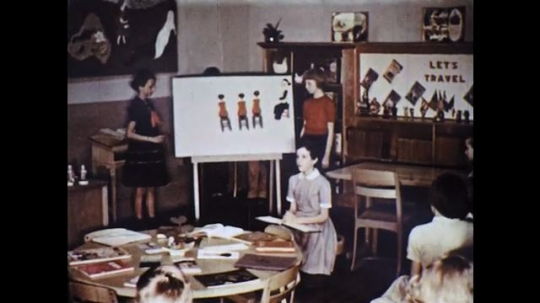 UNITED STATES: 1960s: students tell story to class. Girl takes characters from board.