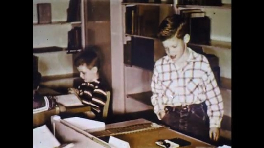 UNITED STATES: 1960s: girl checks out books for student in library. Girl stamps book