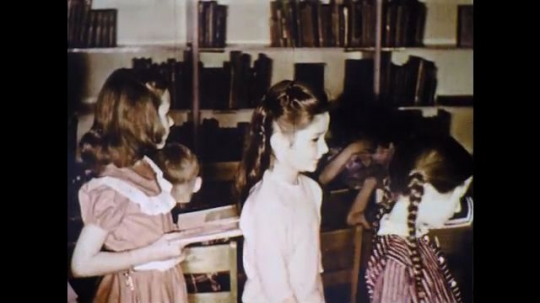 UNITED STATES: 1960s: children line up to take out library books. Child stamps library book. Boy puts card in envelope.