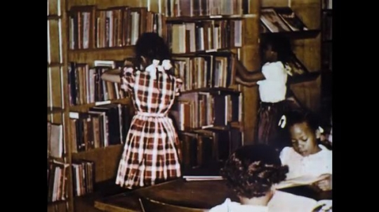UNITED STATES: 1960s: children tidy away library books on shelf. Books on shelf. Folklore books on shelf