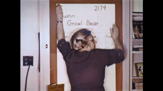 UNITED STATES: 1960s: teacher pins poster to library wall. Austin Growl Bear poster. Borrowers List on wall. Student helps teacher. Children write in books