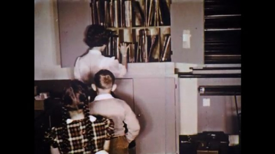 UNITED STATES: 1960s: children help teacher to tidy books in library. Lady shows book to students
