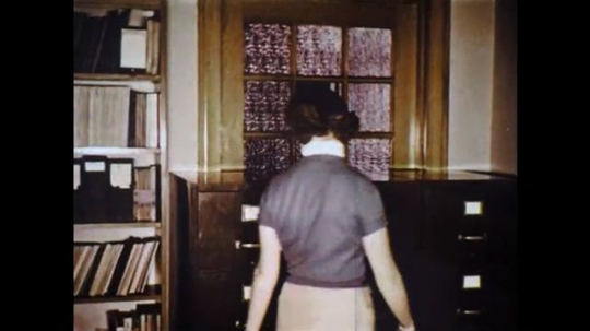 UNITED STATES: 1960s: ladies walk to filing cabinets in library. Photos and pictures in drawer