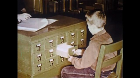 UNITED STATES: 1960s: boy opens drawer. Lady walks across room to desk.