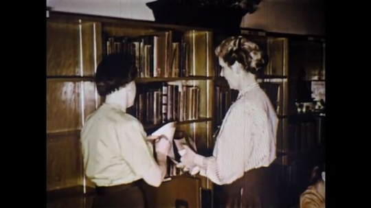 UNITED STATES: 1960s: ladies look through diaries. Child approaches librarian. Lady takes file card from drawer
