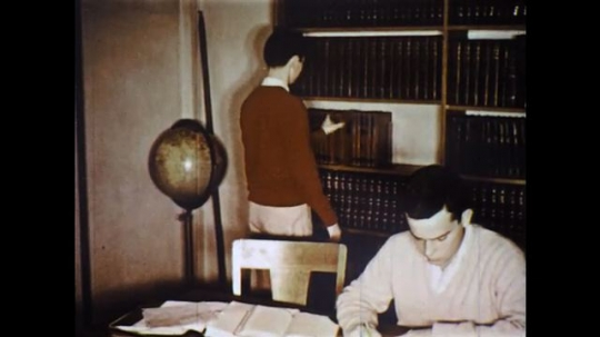 UNITED STATES: 1960s: boy takes book from shelf. Boy looks through pages of book. Boy studies at table