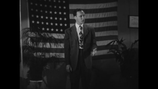 UNITED STATES: 1950s: man presents in front of USA flag.