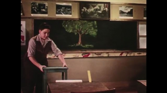 UNITED STATES: 1950s: boy moves table. Boy stretches arms in classroom. Boy flexes muscles