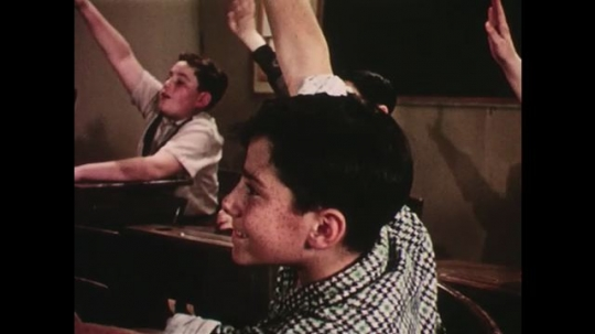UNITED STATES: 1950s: students raise hands in classroom. Boy smiles at desk. Boy comes to front of class