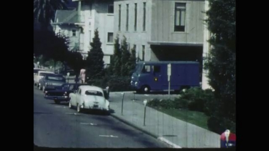 UNITED STATES: 1960s: police car pulls up by building. Police in meeting.