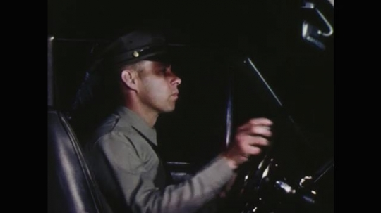 UNITED STATES: 1960s: police officer speaks on radio in car at night. Police man at control station