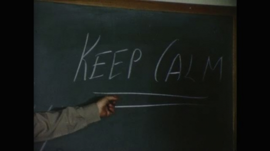UNITED STATES: 1960s: police officer points to keep calm words on blackboard. Police men shake hands after talk
