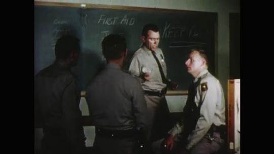 UNITED STATES: 1960s: police officer talks to men after presentation in classroom. Officer sits on desk