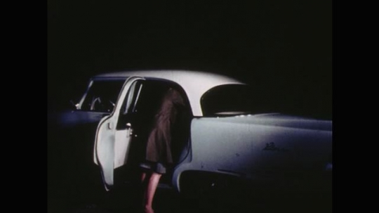 UNITED STATES: 1960s: police officer talks to lady in car at night. Policeman talks to person in car
