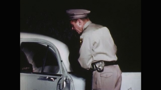 UNITED STATES: 1960s: police officer stands by car. Police Officer holds umbilical cord as placenta delivered. Lady delivers placenta