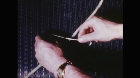 UNITED STATES: 1960s: hands tie string around umbilical cord.