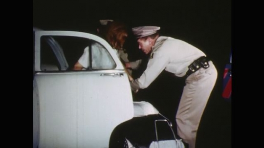 UNITED STATES: 1960s: police officers help lady onto stretcher. Officers put stretcher in car