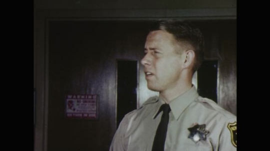 UNITED STATES: 1960s: police man talks to medic at hospital.