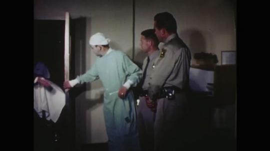 UNITED STATES: 1960s: nurses push lady on hospital trolley. Police man talks to lady
