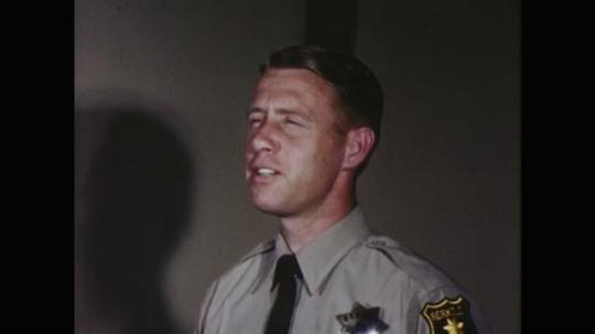 UNITED STATES: 1960s: nurses push lady on hospital trolley. Police man talks to lady. Medic talks to police man