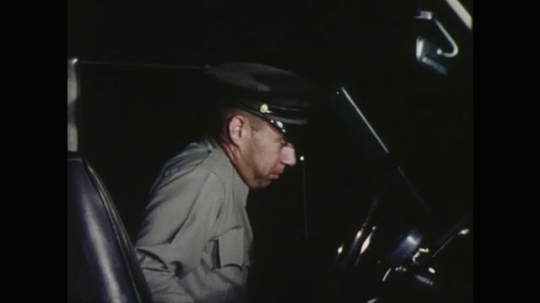 UNITED STATES: 1960s: police officer gets into car. Officer speaks on radio.