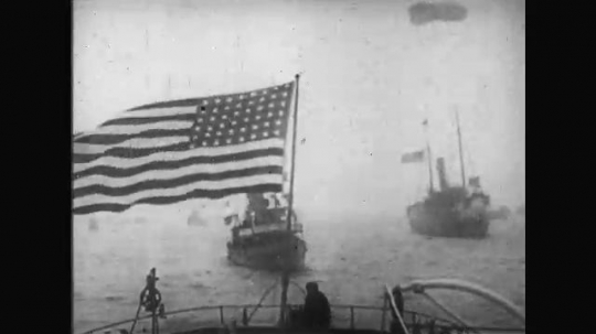 UNITED STATES: 1910s: American flag flies above ship. Waves on ocean. Military fleet at sea. Men up mast of ship.