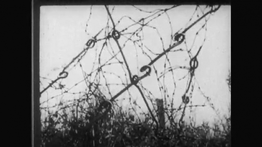 UNITED STATES: 1910s: barbed wire fence. Soldiers hang helmets on trees. Soldiers carry wounded men through trenches.