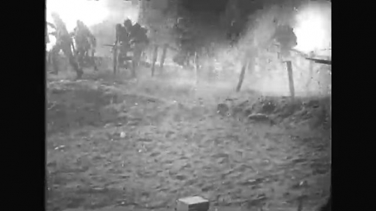 UNITED STATES: 1910s: soldiers run across ground. Soldiers fire guns. Men climb over barbed wire.