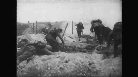 UNITED STATES: 1910s: dead soldier in trench. Soldiers cross ground. Soldiers throw grenades.