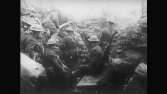UNITED STATES: 1910s: soldiers sit in trench. Soldiers run from trench. Guns fire against soldiers. Explosions on ground.